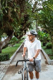 Aziatische jonge man met fietshelmen lopen door straatfietsen