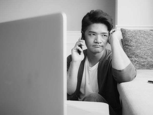 Aziatische jonge man wrijft over zijn vermoeide ogen over zijn smartphone