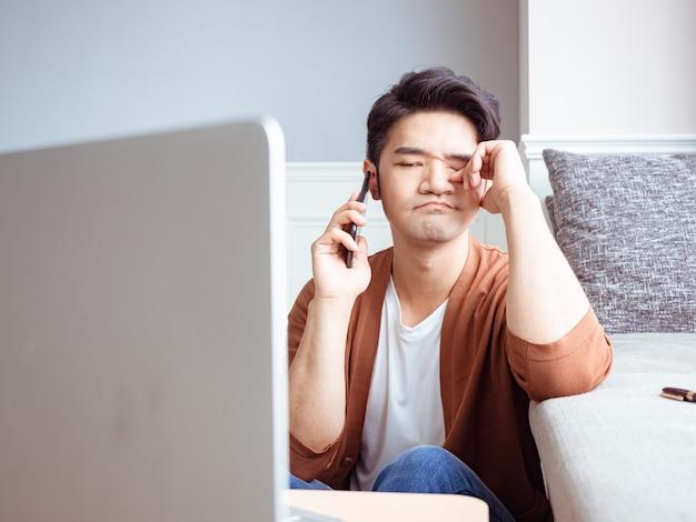 Aziatische jonge man zijn vermoeide ogen wrijven zijn smartphone.