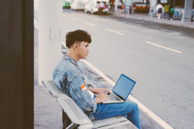Aziatische jonge man zittend op de stoel bij de bushalte van de luchthaven en lustende laptop, zijaanzicht