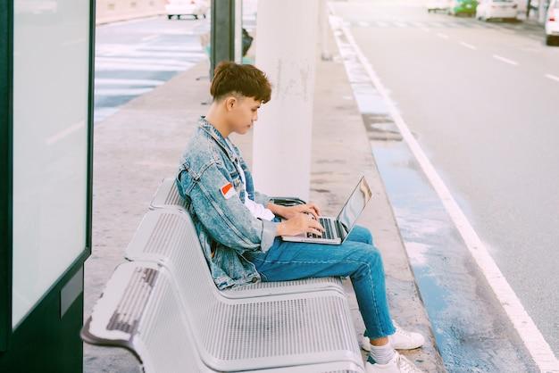Aziatische jonge man zittend op de stoel bij de bushalte van de luchthaven en met behulp van laptop, zijaanzicht