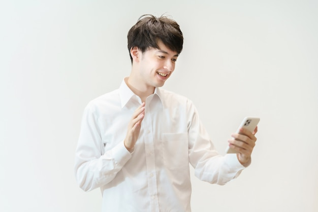 Aziatische jonge man zwaaiend naar zijn smartphone met een glimlach