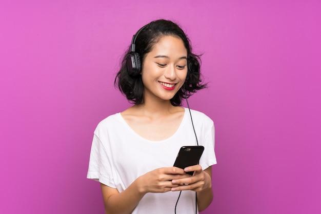 Aziatische jonge meisje het luisteren muziek met mobiel over geïsoleerde purpere muur