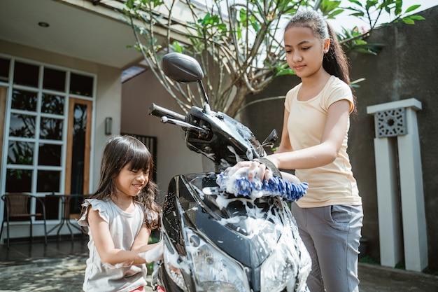 Aziatische jonge meisjes die een motorfiets wassen