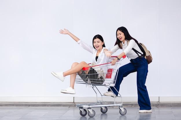 Aziatische jonge meisjeszitting in boodschappenwagentje voor marketing concept