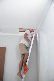 Aziatische jonge mens die een ladder gebruikt om het gebroken plafond thuis te herstellen