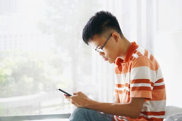 Aziatische jonge mens die oogglas in vrijetijdskleding draagt die in ruimte zit