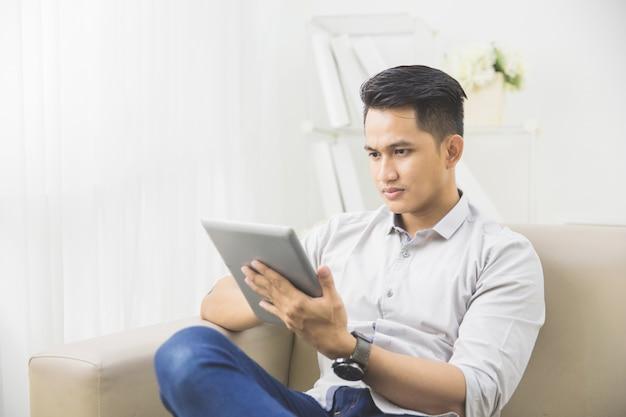 Aziatische jonge mens die tabletpc thuis met behulp van