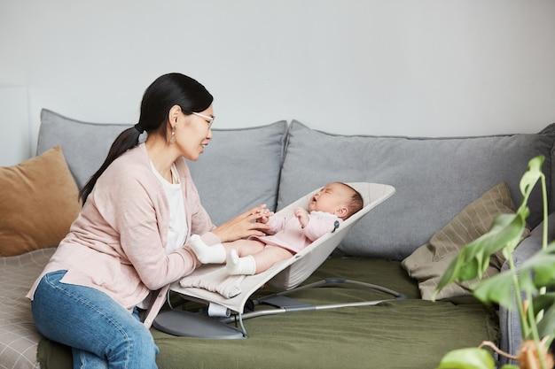 Aziatische jonge moeder die met haar baby praat terwijl ze huilt in de loungestoel in de woonkamer