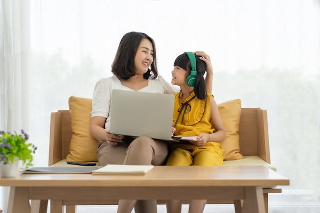 Aziatische jonge moeder met laptop die jong geitje onderwijst om thuis online te leren of te studeren