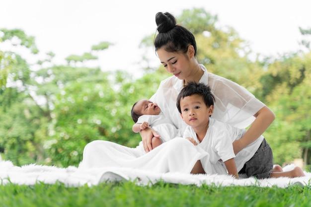 Aziatische jonge mooie moeder die haar pasgeboren baby vasthoudt, slaapt en voelt met liefde en raakt zachtjes aan en zit dan op groen gras in het park