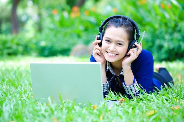 Aziatische jonge mooie vrouw liggen op gras luisteren naar muziek