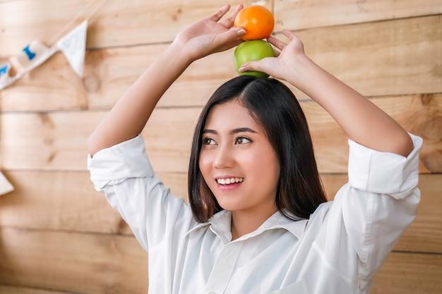 Aziatische jonge mooie vrouwen gelukkige glimlach met appel en oranje fruit witte achtergrond.