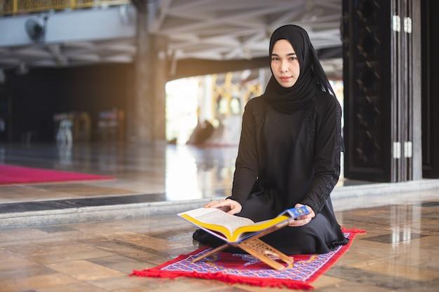 Aziatische jonge moslimvrouw die quran leest, in moskee. in moskee.