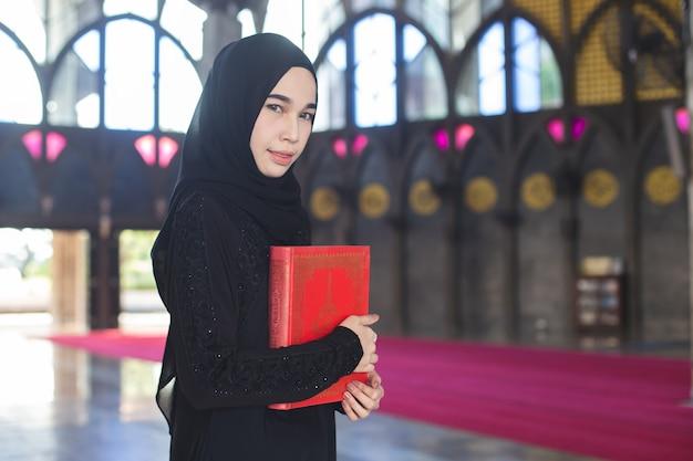 Aziatische jonge moslimvrouw die rode koran, in moskee houdt.