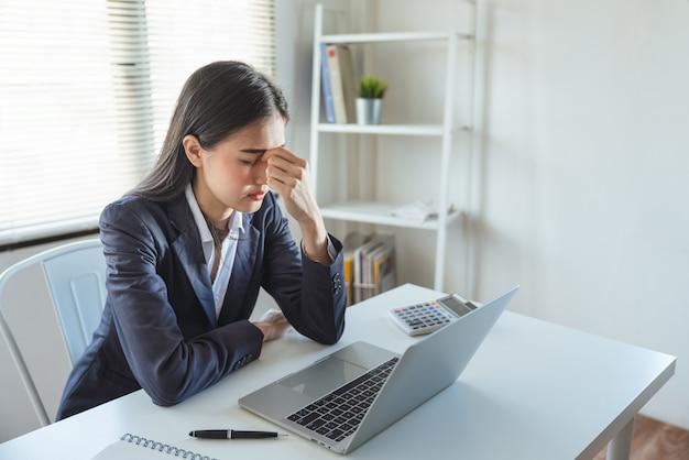 Aziatische jonge onderneemster die spanning en hoofdpijn voelen terwijl het werken met laptop in het het werkbureau