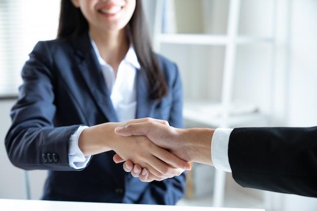 Aziatische jonge onderneemster het glimlachen handdruk met zakenmanpartner die overeenkomstenzaken samen in het het werkbureau maken