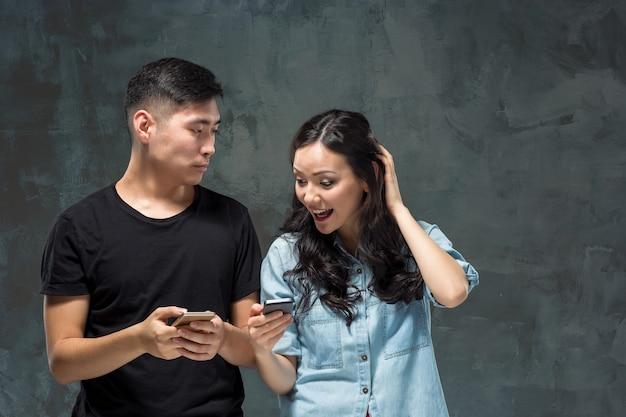 Aziatische jonge paar met behulp van mobiele telefoon, close-up portret.