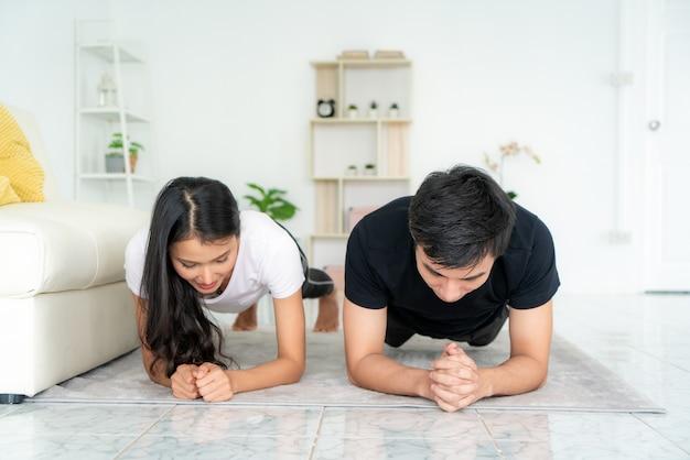 Aziatische jonge paarman en vrouw in sportenkleding die plank doen thuis tijdens training in woonkamer
