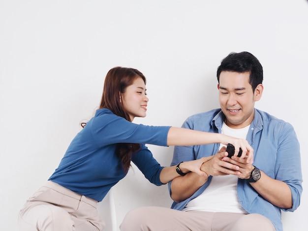 Aziatische jonge paarminnaar die voor een slimme telefoon in woonkamer thuis vechten.