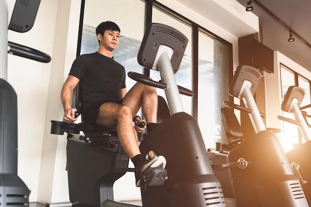 Aziatische jonge sportman die stationaire fiets in fitness gymnastiek berijdt.