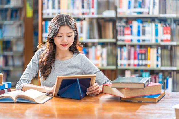 Aziatische jonge student in toevallig kostuum die huiswerk doen en technologieteblet in bibliotheek van universiteit gebruiken