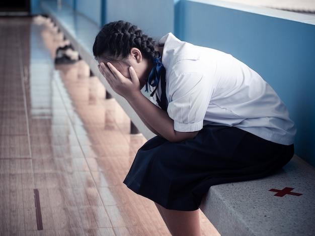 Aziatische jonge studente die alleen met droevig gevoel op school zit