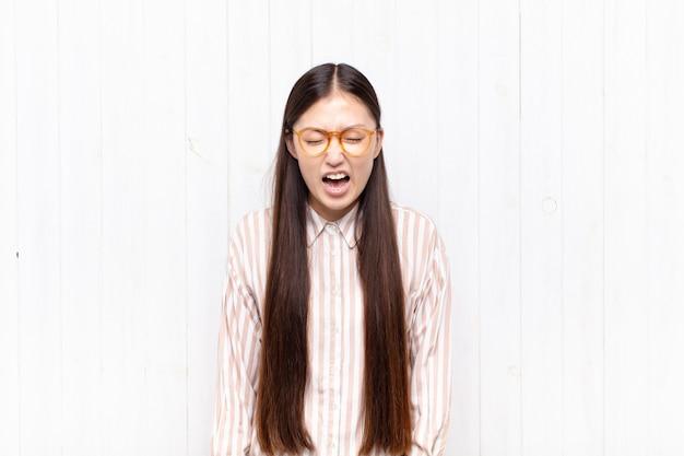 Aziatische jonge vrouw die agressief schreeuwt, erg boos, gefrustreerd, verontwaardigd of geïrriteerd kijkt, nee schreeuwt