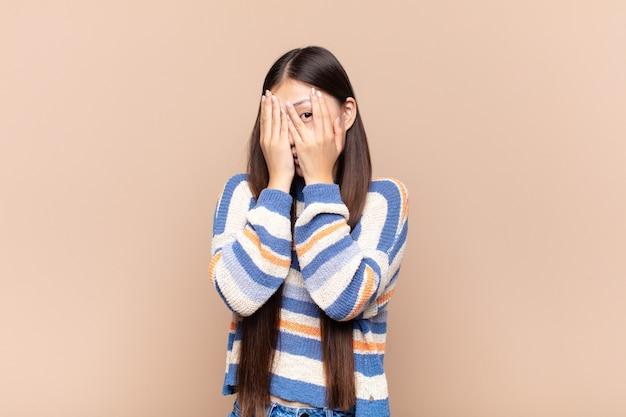 Aziatische jonge vrouw die bang of beschaamd voelt, gluurt of spioneert met ogen half bedekt met handen