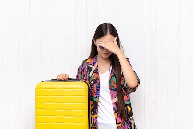 Aziatische jonge vrouw die beklemtoond, beschaamd of overstuur kijkt, met hoofdpijn, gezicht bedekt met hand. vakantie concept
