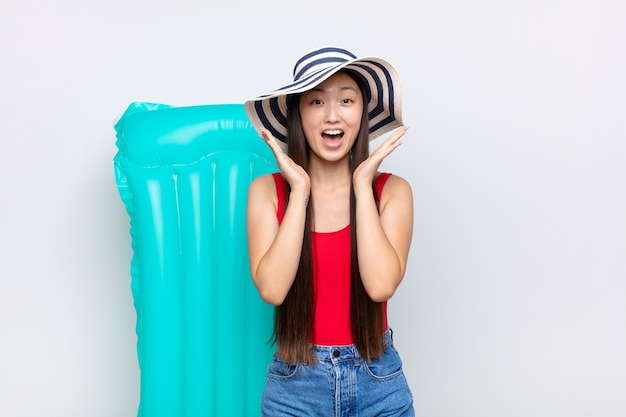 Aziatische jonge vrouw die blij en opgewonden kijkt, geschokt door een onverwachte verrassing met beide handen open naast het gezicht. zomer concept