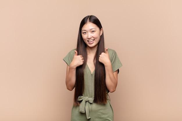 Aziatische jonge vrouw die breed kijkt gelukkig, positief, zelfverzekerd en succesvol, met beide duimen omhoog
