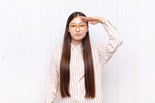Aziatische jonge vrouw die de camera begroet met een militaire groet in een daad van eer en patriottisme, die respect toont