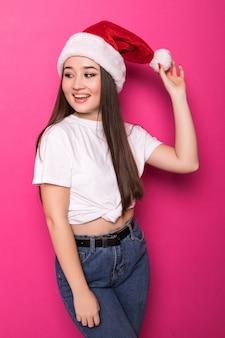 Aziatische jonge vrouw die de hoed van de kerstman draagt die op roze muur wordt geïsoleerd