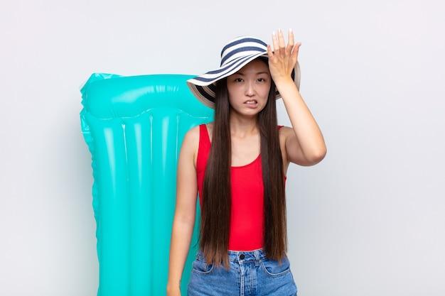 Aziatische jonge vrouw die de palm opheft naar het voorhoofd, denkend oeps, na het maken van een domme fout of het herinneren, zich dom voelen