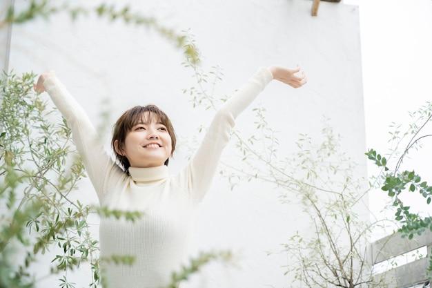 Aziatische jonge vrouw die diep ademhaalt op de veranda