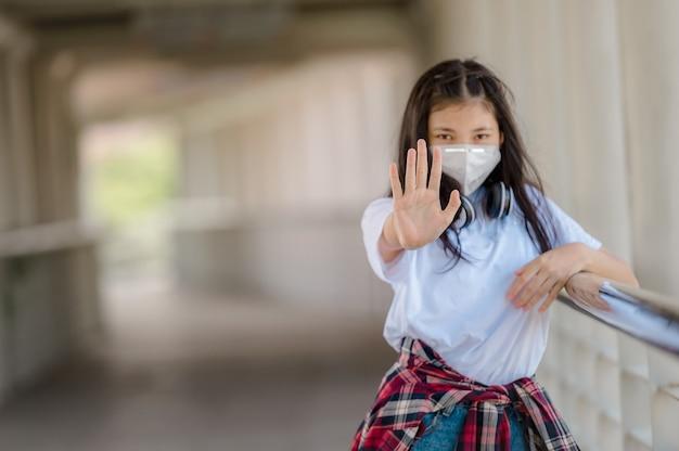 Aziatische jonge vrouw die een beschermend masker draagt tegen coronavirus, covid-19 en mensen stopt om op openbare plaatsen met elkaar in contact te komen, tijdens een virus-corona-pandemie.