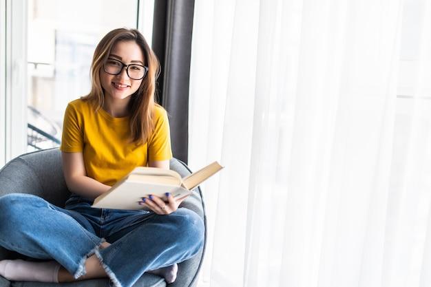 Aziatische jonge vrouw die een boek leest terwijl ze thuis in een moderne fauteuil zit