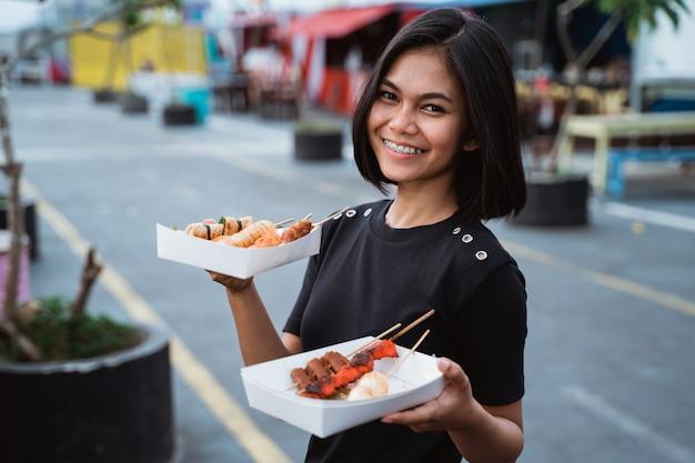 Aziatische jonge vrouw die een geroosterd straatvoedsel draagt