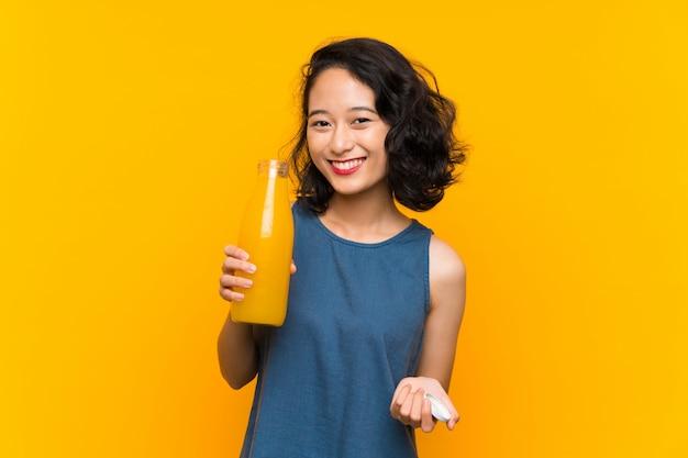 Aziatische jonge vrouw die een jus d'orange houdt
