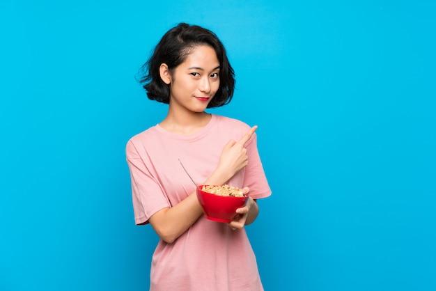 Aziatische jonge vrouw die een kom graangewassen houdt die aan de kant richten om een product te voorstellen