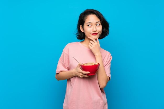 Aziatische jonge vrouw die een kom graangewassen houdt die een idee denken