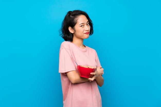 Aziatische jonge vrouw die een kom graangewassen houdt die twijfelsgebaar maken terwijl het opheffen van de schouders