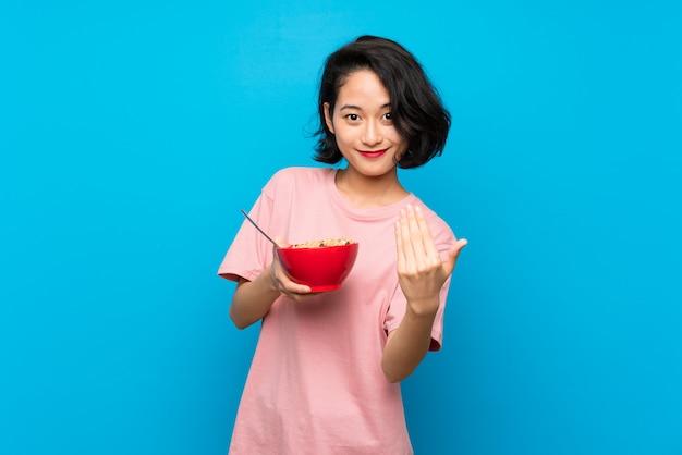 Aziatische jonge vrouw die een kom graangewassen houdt die uitnodigt om met hand te komen, gelukkig dat u kwam