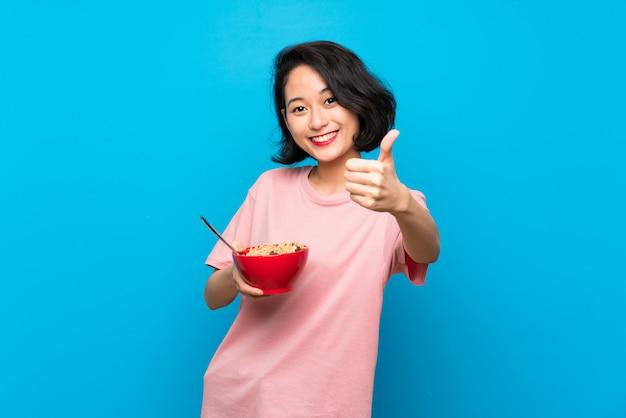 Aziatische jonge vrouw die een kom graangewassen met omhoog duimen houdt omdat iets goeds is gebeurd