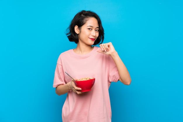 Aziatische jonge vrouw die een kom graangewassen trots en zelf-tevreden houdt