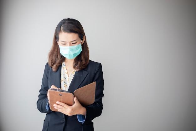 Aziatische jonge vrouw die een tablet gebruikt om vanuit huis te werken en een antivirusmasker te dragen om anderen tegen coronavirus te beschermen