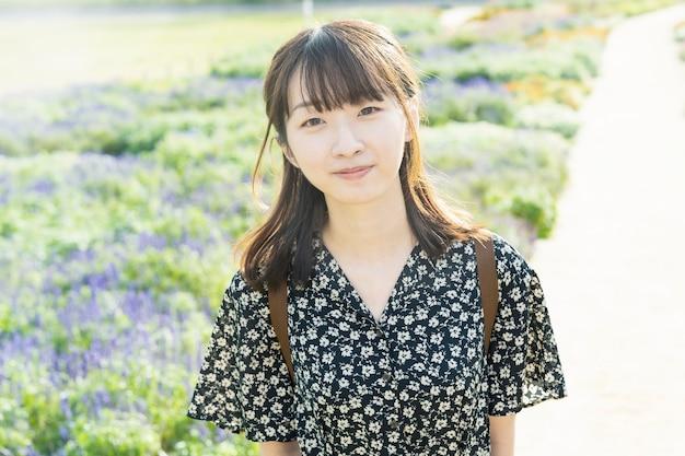 Aziatische jonge vrouw die een wandeling op een bloemgebied maakt