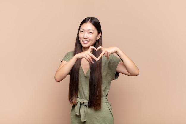 Aziatische jonge vrouw die en gelukkig, leuk, romantisch en verliefd glimlacht voelt en hartvorm maakt