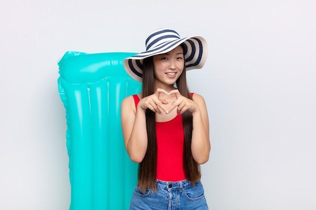 Aziatische jonge vrouw die en gelukkig, leuk, romantisch en verliefd glimlacht voelt en hartvorm met beide handen maakt. zomer concept